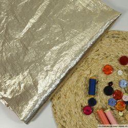 Tissu polyester lamé or pâle