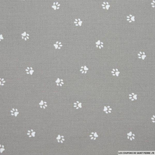 Tissu Piqué de coton imprimé pattes de chien blanches sur fond gris