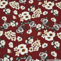 Coton imprimé fleurs de mystère fond rouge